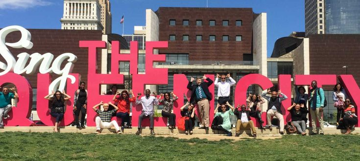 Group of people in front of Sing Queen City Sign